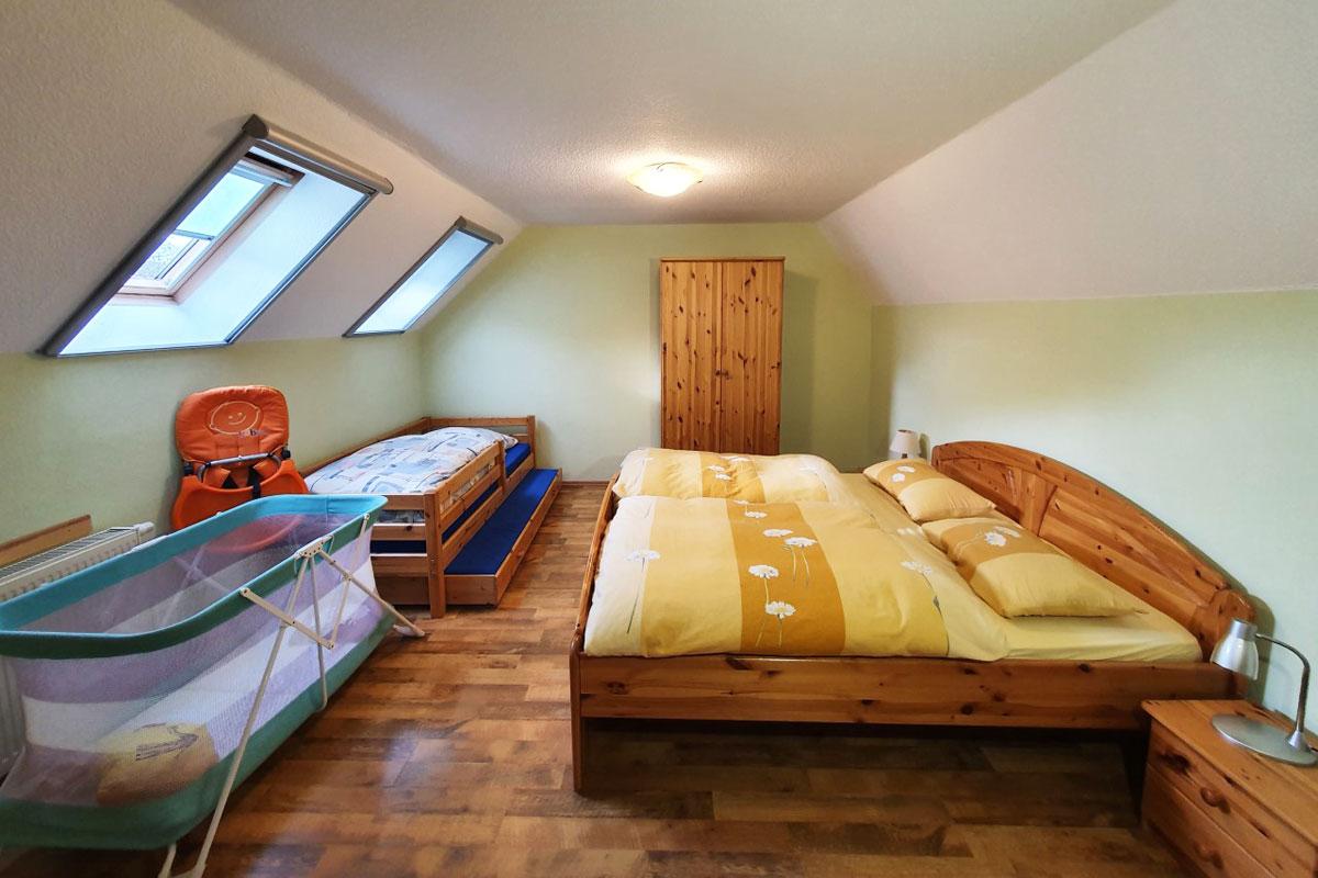 Ferienwohnung Abendrot - großes Schlafzimmer mit Doppelbett und Kinderbett